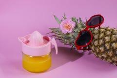 Serie dell'ananas con gli occhiali da sole su fondo blu e rosa giallo immagine stock