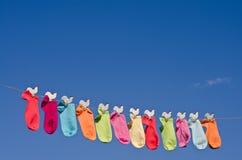 Serie di calzini variopinti contro cielo blu Fotografie Stock Libere da Diritti