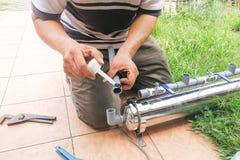 Serie di idraulico che ripara sul filtro da acqua all'aperto con la conduttura del PVC immagini stock
