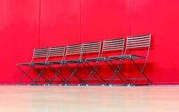 Serie krzesła przeciw czerwieni ścianie Zdjęcie Stock