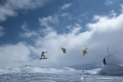 Serie of a snowboarder. Jumping high in the air while performing a grab Stock Photos