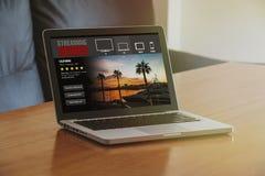 Serie televisiva che scorre servizio: Computer portatile con il flusso continuo del sito Web video di servizio nello schermo Fotografia Stock