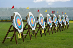 Series of archery clear targets in green field. Series of straw archery targets in wooden stands inside football stadium Stock Images