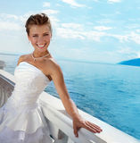 Series: Beautiful Bride at the water view. Beautiful bride wearing a fancy wedding dress, looking at camera in the sunny day at the water view Royalty Free Stock Photo