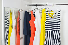 A series of bright modern fashion women's dresses on hangers in Stock Photography