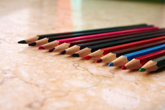A series of colored pencils on a brown marble Royalty Free Stock Photography