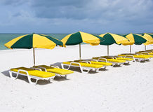 Series of colorful lounge chairs on a white sand. A series of yellow lounge chairs with green and yellow parasols, on a pristine white sand beach Royalty Free Stock Photo