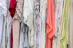 Series of female summer dresses hanging on a hanger on the market for sale Stock Images