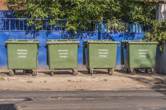 A series of four waste containers. Four plastic waste containers arranged in a row on a city street Stock Photo