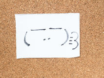 The series of Japanese emoticons called Kaomoji, smug. The series of Japanese emoticons called Kaomoji on the cork board, smug Stock Photography