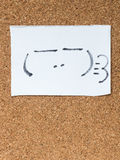 The series of Japanese emoticons called Kaomoji, smug. The series of Japanese emoticons called Kaomoji on the cork board, smug Royalty Free Stock Photography