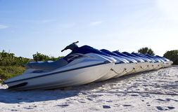 Series of Jet-Ski watercraft on a tropical beach. A series of Jet-Ski parked on a tropical beach Stock Images