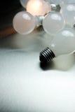 Series of lightbulbs. On metal desk Royalty Free Stock Photography