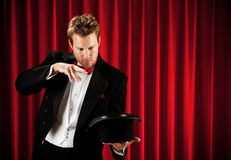 Magician: Ready to Pull Rabbit Out of Hat. Series about a magician in a traditional tuxedo, with various props, looking mysterious and magical royalty free stock photos