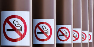 Row of No Smoking signs on series of columns. Series of No Smoking signs mounted on columns with diminishing perspective for a healthy smoke free environment stock photo