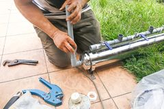 Series of plumber fixing up outdoor water filter with pvc piping Stock Photography