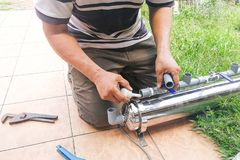 Series of plumber fixing up outdoor water filter with pvc piping Stock Images