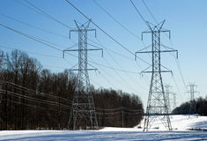 Series of  Power Line Towers. Series of white power line towers fading into the distance. This could illustrate smart grid technology Royalty Free Stock Image