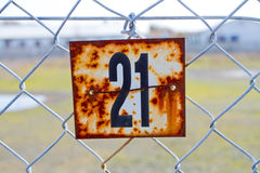 Number 21 Rusted Sign. A series of rusted old signs or tags are attached to this chain link fence with orange and white rust and the numbers clearly visible Royalty Free Stock Images