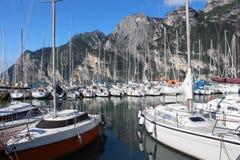 Series of sailboats, dock at Lake Garda, Italy. Two rows of sailboats at Lake Garda, Italy, under the mountains Royalty Free Stock Photo