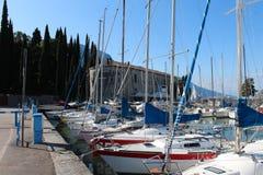Series of sailboats, dock at Lake Garda, Italy. Two rows of sailboats at Lake Garda, Italy, under the mountains Royalty Free Stock Images