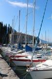 Series of sailboats, dock at Lake Garda, Italy. Two rows of sailboats at Lake Garda, Italy, under the mountains Stock Image