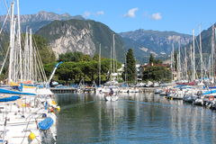 Series of sailboats, dock at Lake Garda, Italy. Two rows of sailboats at Lake Garda, Italy, under the mountains Royalty Free Stock Photography