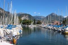 Series of sailboats, dock at Lake Garda, Italy. Two rows of sailboats at Lake Garda, Italy, under the mountains Royalty Free Stock Image