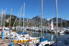 Series of sailboats , dock at Lake Garda, Italy. Two rows of sailboats at Lake Garda, under the mountains, in Italy Stock Photography