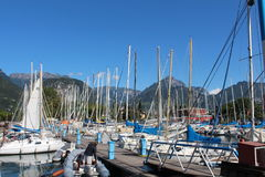 Series of sailboats and motorboat, dock at Lake Garda, Italy. Two rows of sailboats at Lake Garda and motorboat, under the mountains, in Italy Royalty Free Stock Image