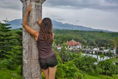 Series traveling girl in Asia. beautiful girl with long dark hair in elegant grey dress posing on old bridge in Tirta. Gangga water temple in Bali royalty free stock images