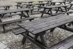 Tavern style forniture. Series of wet empty wood tavern style tables Stock Photography