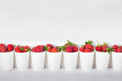 A series of white paper cups with fresh ripe delicious sweet str Stock Image
