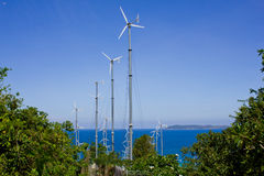 Series of wind power generators in clear blue sky background. Stock Photo