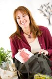 Reusable: Woman Unpacks Steak From Fabric Bag. Series with a woman unpacking groceries and using reusable fabric bags Stock Image