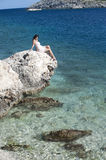 Series of a women on a rock. Series of a beautiful woman looking into the distance sitting on a rock in the sea Royalty Free Stock Images