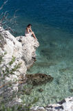 Series of a women on a rock. Series of a beautiful woman looking into the distance sitting on a rock in the sea. View from top Royalty Free Stock Photo
