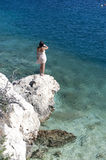 Series of a women on a rock. Series of a beautiful woman back sitting on a rock in the Ionian sea. View from top Stock Photos