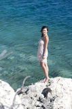 Series of a women on a rock. Series of a beautiful woman sitting on a rock in the Ionian sea -Zakynthos. View from top Stock Photography