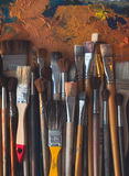 Series of wooden different size paintbrushes lying on palette with old oil paint cracked texture in art studio, top view Stock Images