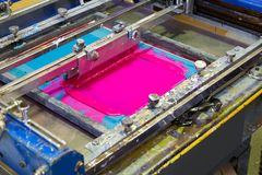 Serigraphy Printer ink machine pink magenta color. In printing factory royalty free stock images