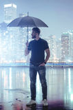 Serine man holding umbrella in abstract metropolis Royalty Free Stock Image