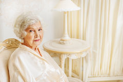 Serine rich old woman sitting on armchair Stock Photography