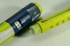 A seringa da insulina ou o injetor do modelo da pena com o botão do ajuste da dose e a janela da escala e de uma uma estadia joga fotos de stock