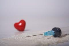 Seringa e comprimidos apresentados sob a forma do coração em um fundo branco Foto de Stock Royalty Free