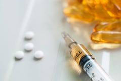 Seringa e comprimidos coloridos Fotografia de Stock Royalty Free