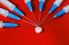 Seringa Hypodermic Seringas com agulhas azuis em um fundo vermelho Injetores médicos Imagem de Stock Royalty Free