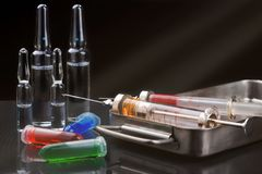 Seringas com a medicamentação na caixa, nas ampolas e nos tubos de ensaio da esterilização com líquido no backround escuro com ra Fotografia de Stock Royalty Free