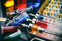 Seringas com a medicamentação na caixa, nas ampolas e nos tubos de ensaio da esterilização com líquido na superfície lustrosa ton Imagem de Stock