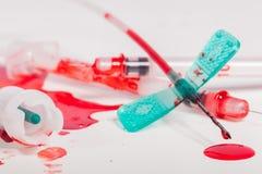 Seringas e IV linhas cobertas com o sangue Fotos de Stock